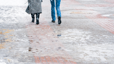 Winter City Slippery Sidewalk. Back view on the feet of people walking along the icy snowy pavement. Pair of shoe on icy road in winter. Abstract empty blank winter weather background