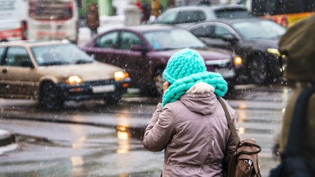 Woman in an urban environment at the crossroads talking on the phone. Huge knitted scarf and hat in turquoise color. Snowfall. Winter weather background Archivio Fotografico