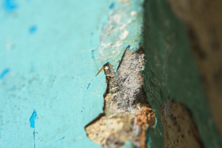 Peeling Blue Aquamarine Color Paint from Outer Corner of the Wall. Shattered Plaster Background. Abstract Blurry Backdrop