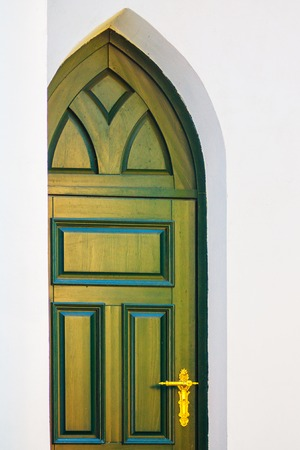 Beautiful Green Wooden Doors in Gothic Style with Gilded Fittings in White Wall Фото со стока