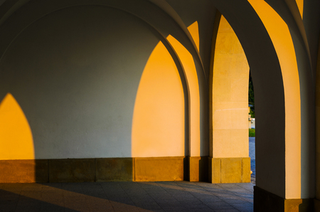 Corridor Colonnade Arcade Perspective Architectural Background. Arched Vaults in Architecture.Building Exterior at Sunset Фото со стока
