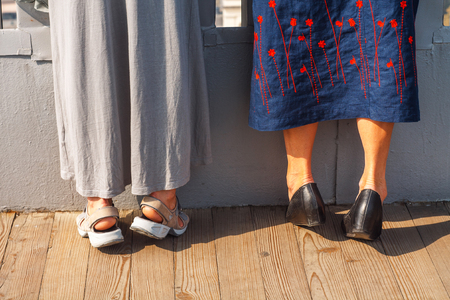 Two Adult Women in Long Skirts Standing on Tiptoes. Curiosity Peeping Concept. Stock Photo