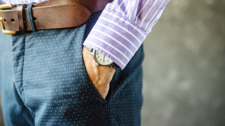 Close Up of Man Hand with Wrist Watch in the Pocket of Stylish Pants Close Up. Fashion Portret of Businessman in Striped Shirt. Accessories for Men Style. Fashion and punctuality concept