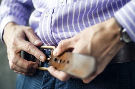 Young Man in a Striped Shirt Puts on a Belt in Trousers Close Up. Put on Clothes Concept