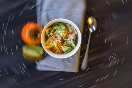 Top View of the Oatmeal with Fresh Persimmon, Kiwi, Walnut and Sesame. Abstract Blured in a Circular Motion Colorfull Food Background 스톡 콘텐츠