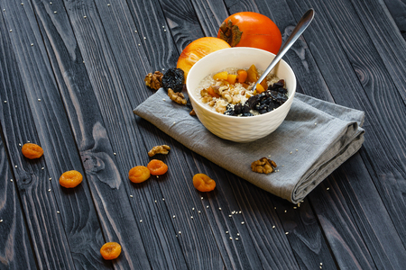 Oatmeal with Persimmon, Prune, Dried Apricots, Walnut and Sesame on a Black Wooden Table Top View Copy Space Background 版權商用圖片