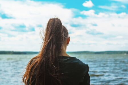 Junge Frau mit langen braunen Pferdeschwanzhaaren steht an der Küste und schaut in die Ferne. Silhouette einer Mädchenansicht von hinten auf dem Hintergrund des Meereshorizonts Standard-Bild