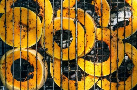 Baked pumpkin slices on the grill grid. The process of cooking vegetables on the grill in the open air