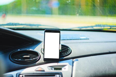Smartphone on the front of the car as a navigator. Cut out the white background of the screen of the smartphone for placing graphics