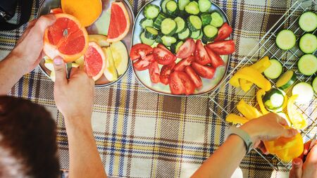 Outdoors top view on the checkered tablecloth during cooking process. A man cutting vegetables and fruits at a picnic
