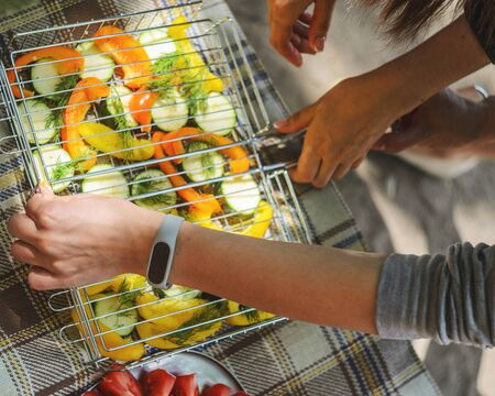Woman are fill grill lattice with slices of zucchini, pepper and dill before roasting