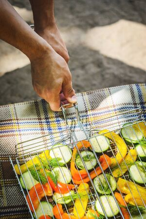 Man hold grill lattice with slices of zucchini, pepper and dill before roasting