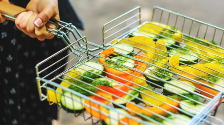 Woman hold grill lattice with slices of zucchini, pepper and dill before roasting