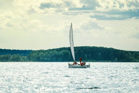 A small sailing yacht goes to the bay on a sunny day against the backdrop of a dense forest on the opposite shore.