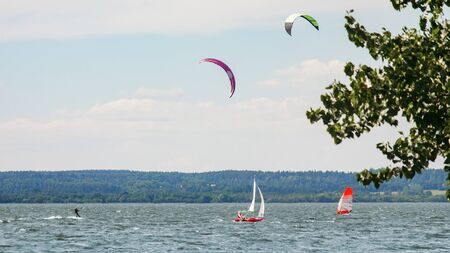Kitesurfer, windsurfer and small sailboat sailing past each other. A variety of outdoor activities on water concept