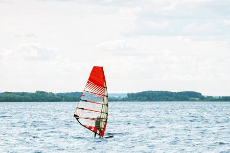 Windsurfer stands on the board and tries to catch a gust of wind Reklamní fotografie
