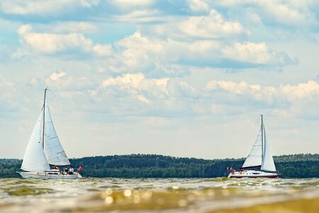 Two sailing yachts goes to the bay on a sunny day against the backdrop of a dense forest on the opposite shore.