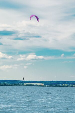 A kiteboarder is pulled across water by a power kite. Kitesurfer high in flight
