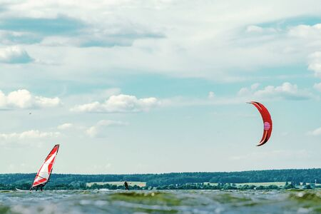 Kitesurfer and windsurfer sailing past each other. A variety of outdoor activities on water concept