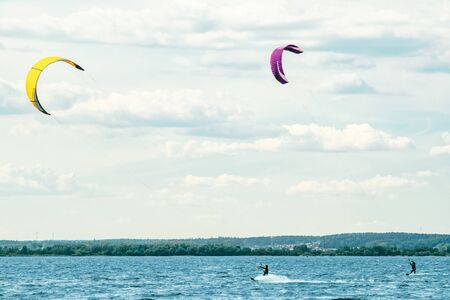 Two kiteboarders is pulled across water by a power kites, trying to leave without crash