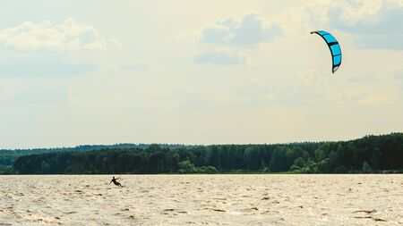 A kiteboarder is pulled across water by a power kite Фото со стока