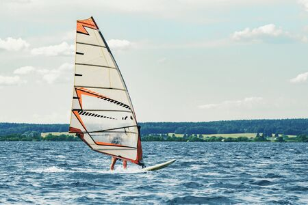 Windsurfer catches the wind and cuts the waves while driving fast