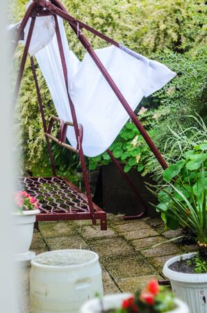 Metal swing in the yard after a rainstorm. Rainwater filled the white canopy from the sun