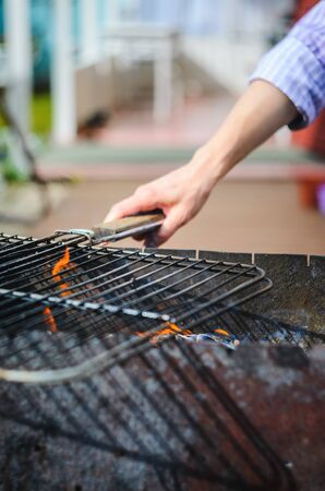 A hand is holding an empty grill grid on the coals. Barbecue background with empty space