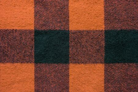 Fabric with black and orange cages pattern. Plaid material. Clothes background