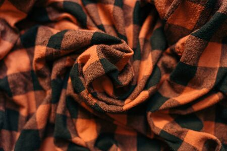 Fabric with black and orange cages pattern. Plaid material. Clothes background. Crumpled Cloth Blank Background