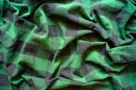 Fabric in a cage. Black and green square pattern. Crumpled Cloth Blank Background