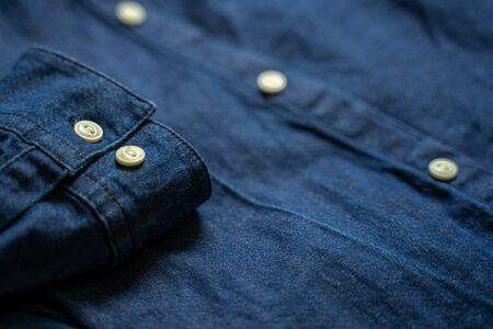 Blue denim shirt cuff with white buttons close-up. Garment background