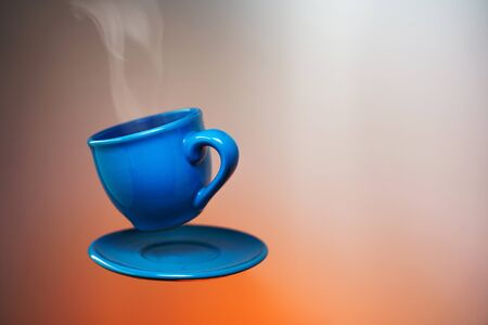 Floating blue cup of espresso. Mock up of soaring in the air cup of hot coffee 免版税图像