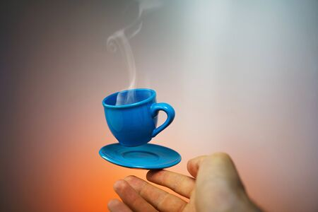 Floating blue cup of espresso with hands. First-person view. Mock up of soaring in the air cup of hot coffee. Levitate concept