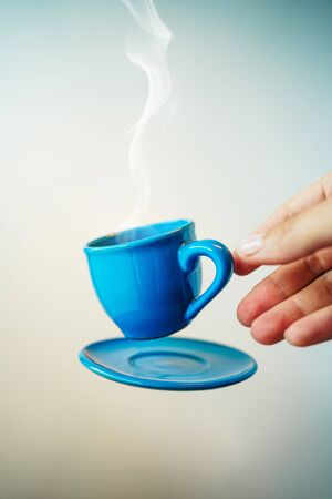 Floating blue cup of espresso with hand. Mock up of soaring in the air cup of hot coffee. Levitate concept 免版税图像