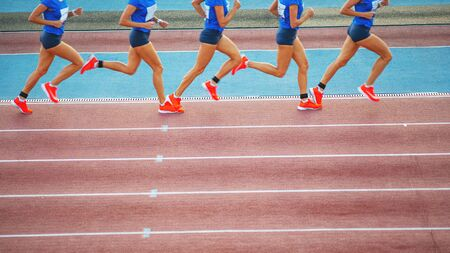 Female athlete runs on the athletic track. Running movement phases concept.