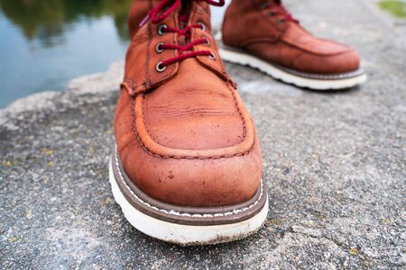 Water drops on red leather work boots close-up. The concept of water-repellent impregnation for leather shoes