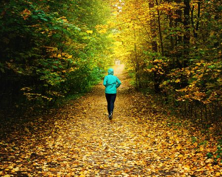 A woman athlete run in the autumn forest. Jogging in an amazing autumn forest strewn with fallen leaves 版權商用圖片 - 132621000