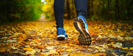 Jogger's feet in blue sneakers close up. A woman athlete run in the autumn forest. Jogging in an amazing autumn forest strewn with fallen leaves 版權商用圖片 - 132621414