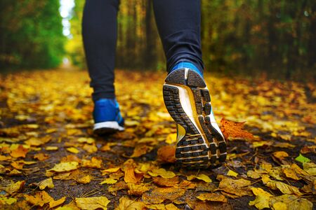 Jogger's feet in blue sneakers close up. A woman athlete run in the autumn forest. Jogging in an amazing autumn forest strewn with fallen leaves 版權商用圖片 - 132621470