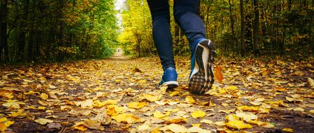 Jogger's feet in blue sneakers close up. A woman athlete run in the autumn forest. Jogging in an amazing autumn forest strewn with fallen leaves 版權商用圖片 - 132621142
