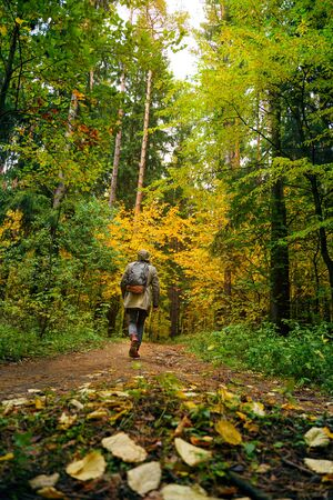 A man with backpack walks in the amazing autumn forest. Hiking alone along autumn forest paths. Travel concept. 版權商用圖片 - 132626216