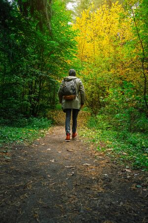 A man with backpack walks in the amazing autumn forest. Hiking alone along autumn forest paths. Travel concept. 版權商用圖片 - 132621917