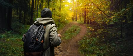 A man with backpack walks in the amazing autumn forest. Hiking alone along autumn forest paths. Travel concept. 版權商用圖片 - 132623000