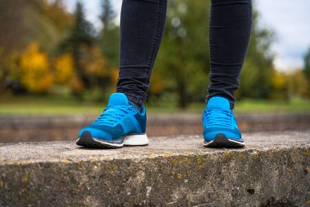 Blue sneakers on a woman legs. Outside workout in running shoes concept 版權商用圖片 - 132622056