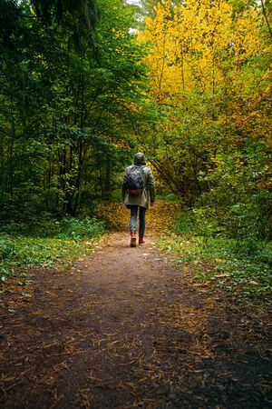 A man with backpack walks in the amazing autumn forest. Hiking alone along autumn forest paths. Travel concept. 版權商用圖片 - 132622536