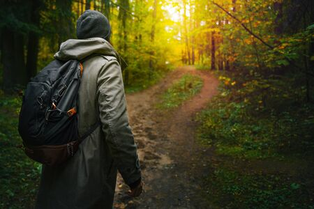 A man with backpack walks in the amazing autumn forest. Hiking alone along autumn forest paths. Travel concept. 版權商用圖片 - 132623066