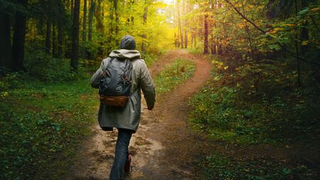 A man with backpack walks in the amazing autumn forest. Hiking alone along autumn forest paths. Travel concept. 版權商用圖片 - 132622643