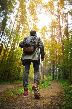 A man with backpack walks in the amazing autumn forest. Hiking alone along autumn forest paths. Travel concept. 版權商用圖片 - 132622777
