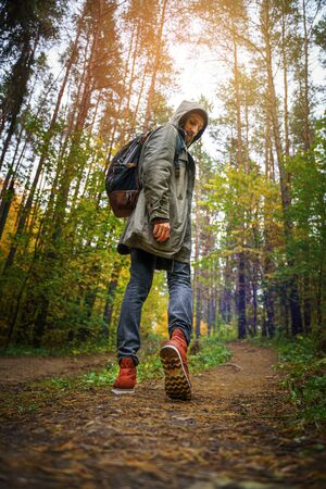 A man with backpack walks in the amazing autumn forest. Hiking alone along autumn forest paths. Travel concept. 版權商用圖片 - 132622287